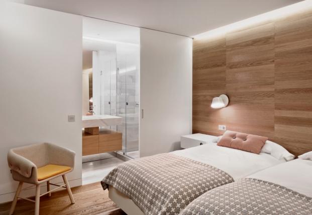 cabecero de madera en apartamento en madrid con obras de arte