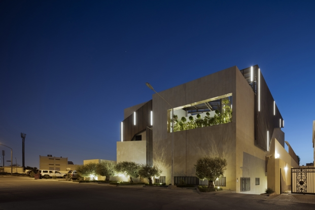 vista nocturna del exterior de una casa con jardines por AGi architects diariodesign