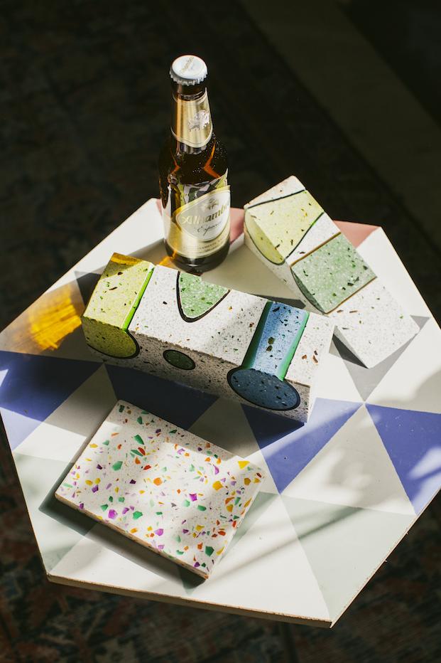 piezas de terrazo y botella de cervezas alhambra