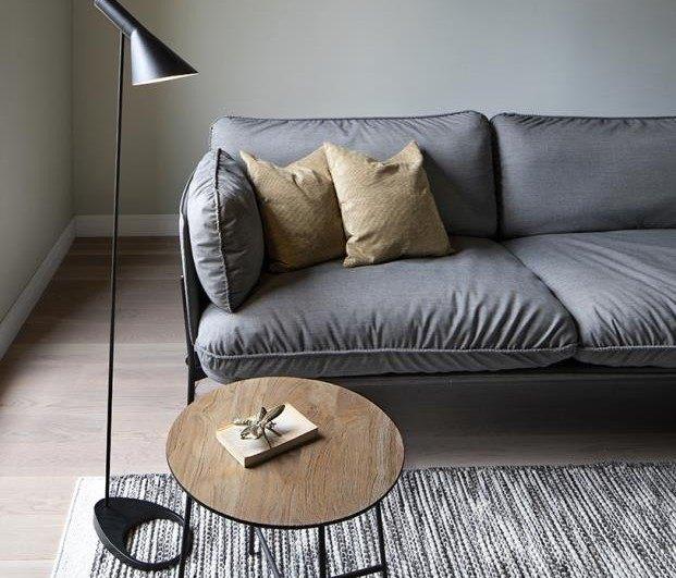 sofa-gris-paredes-verdes-lapara-de-pie-negra-lectura