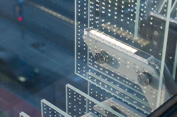 detalle anclaje de cristal en fachada con estructura metálica