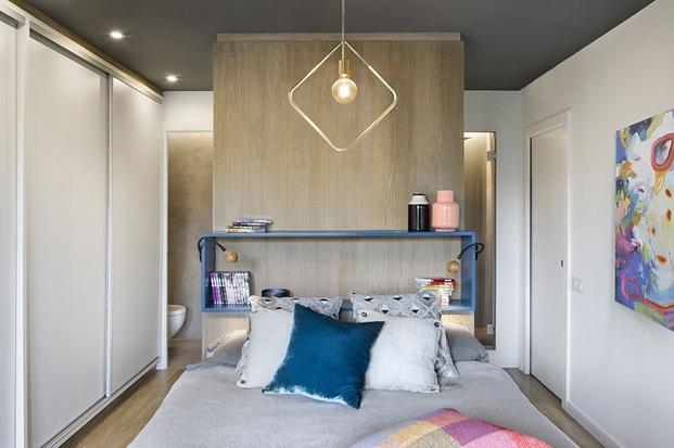 dormitorio con baño tras la cama