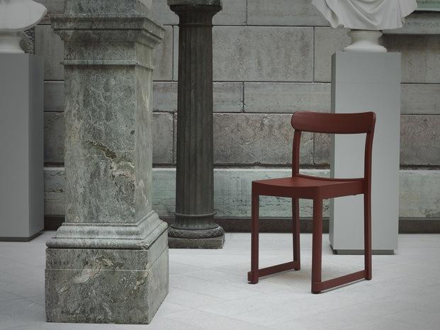 silla granate al lado de columna de piedra