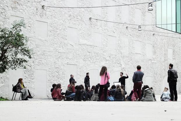 Grupo de visitas con guía explicación pared blanca diariodesign