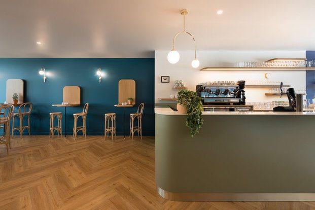 Barra de bar verde, lámpara art decó y pared azul con taburetes bitró Brasserie Camille diariodesign