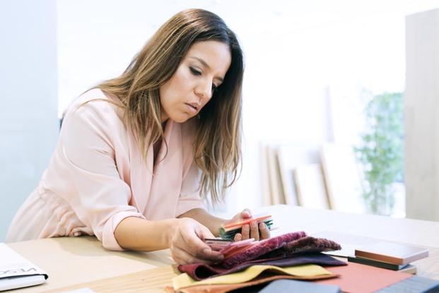 chica con vestido rosa mirando carta de materiales