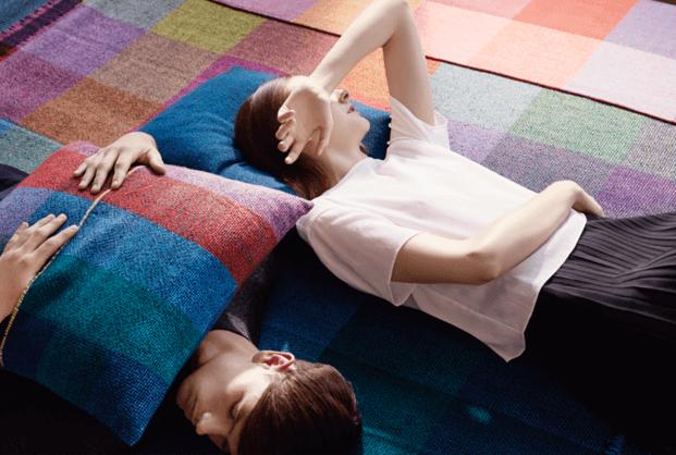 Chico y chica tumbados en el suelo con cojines de lana de colores zuzunaga diariodesign