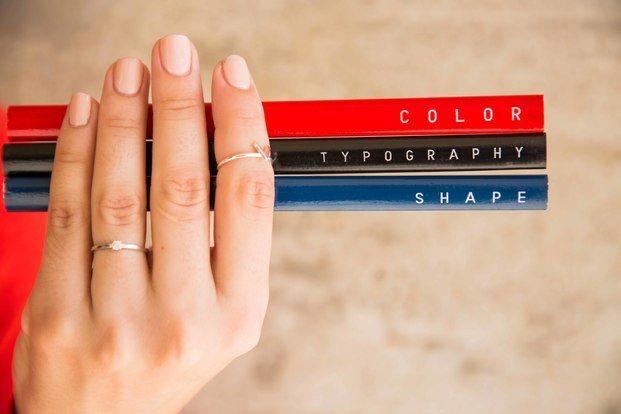 Mano sujetando tres lápices rojo, negro y azul diariodesign