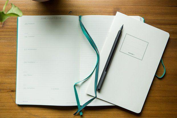Agenda semana vista abierta sobre mesa de madera diariodesign