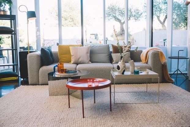 sofá gris con cojines y tres mesas de centro estilo nordico diariodesign