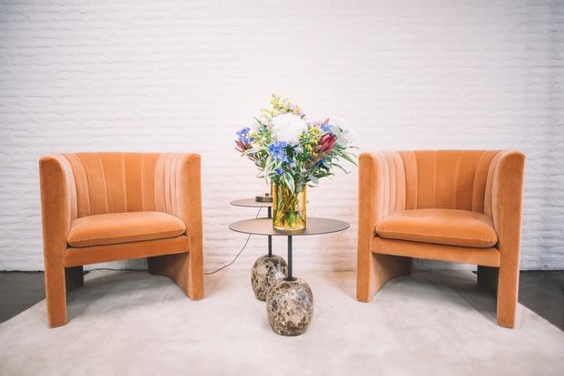 Dos butacas vutage de terciopelo marrones con mesita con flores diariodesign