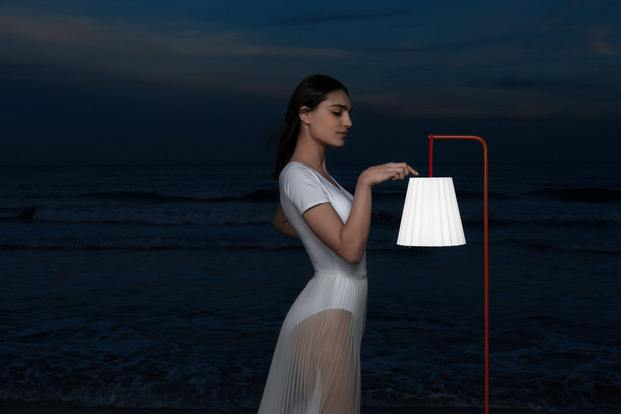 Chica sobre fonde de mar azul oscuro con una lámpara portable