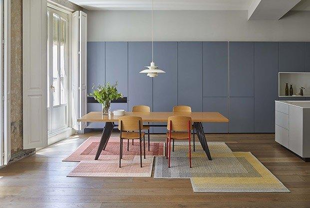 Comedor con mesa de madera y alfombra de diseño