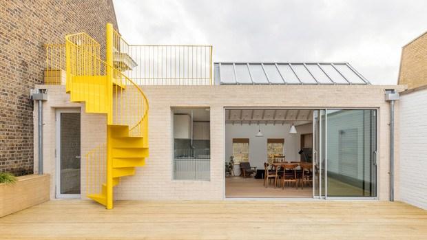 Casa con escalera de caracol amarilla en el exterior