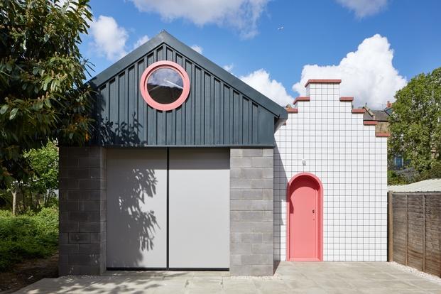 Edificio con dos volúmenes. Cemento gris y baldosas blancas con detalles rosas. Lomax Studio. Londres