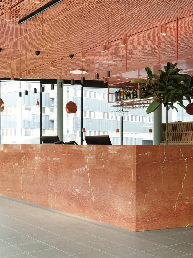 Grow Hotel Estocolmo. Note Design Studio. Recepción de hotel con mármol y techo color melocotón