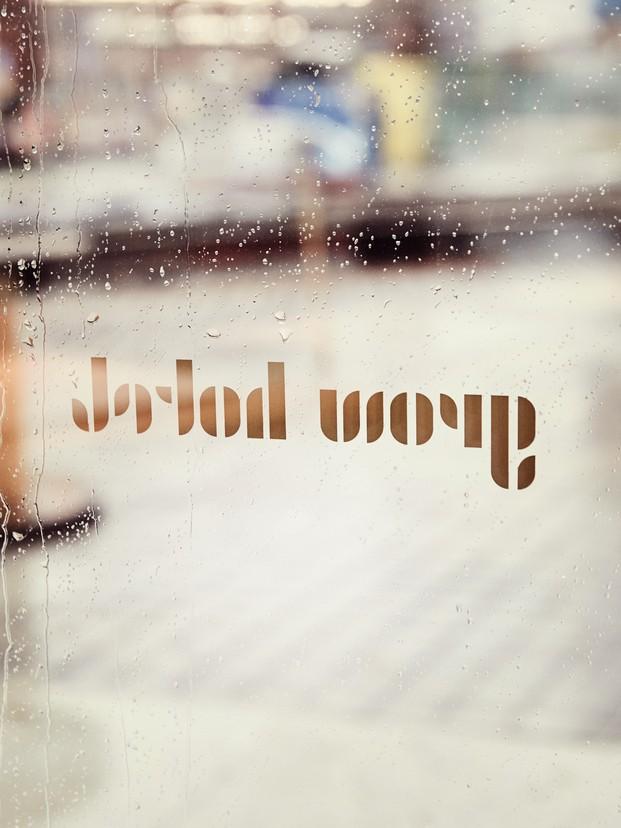 Grow Hotel Estocolmo. Note Design Studio. Vinilo de letras doradas sobre cristal con gotas de lluvia