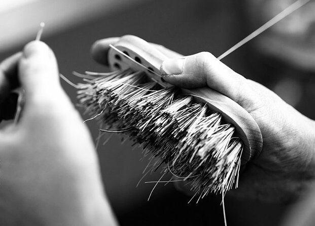 Manos fabricando un cepillo de cerdas
