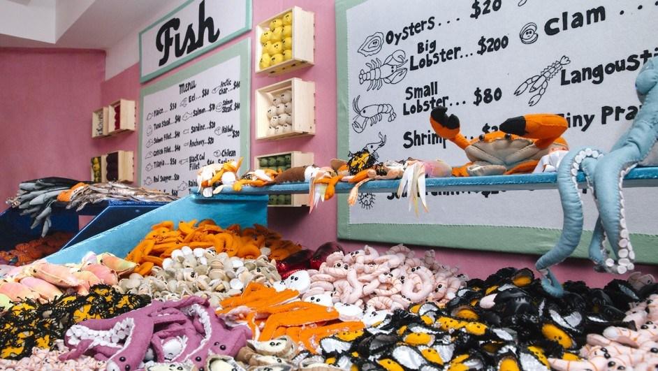 Lucy Sparrow inaugura Delicatessen 6th en el Rockefeller center, donde recrea productos alimenticios usando fieltro.