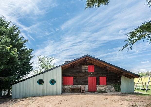 una casa de campo con ventanas y puertas rojas