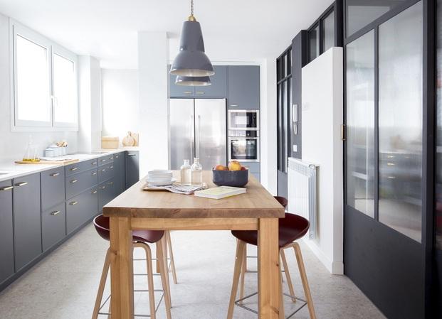 Cocina gris con mesa alta de madera