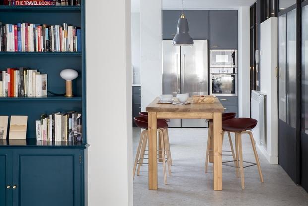 Cocina con mesa alta de madera y taburetes granate