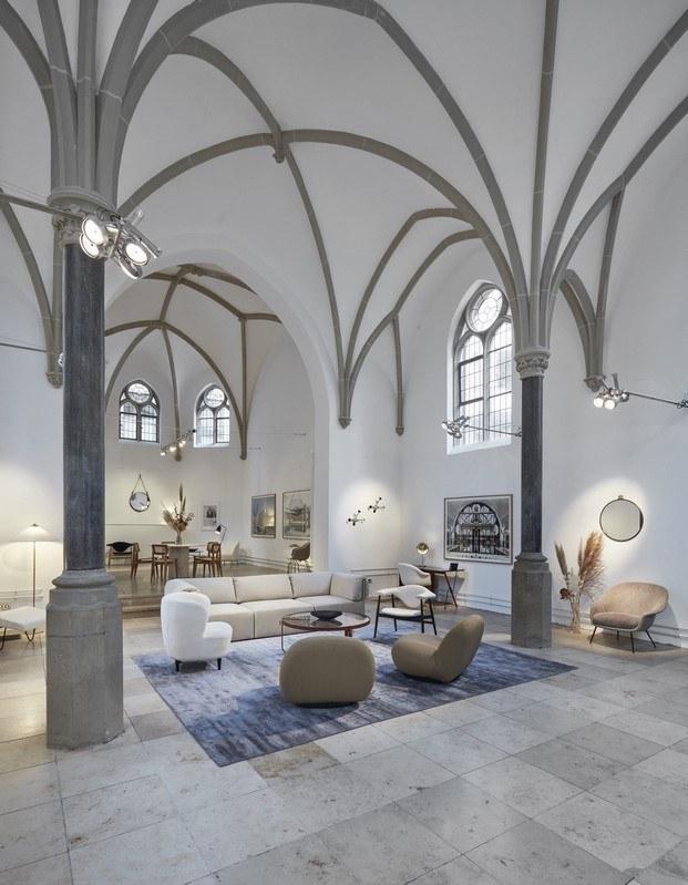 salón de diseño en una capilla diseñado por gubi con butacas pacha de pierre paulin