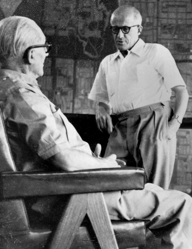 Pierre Jeanneret habla con Le Corbusier, sentado en un sillón Capitol Cassina