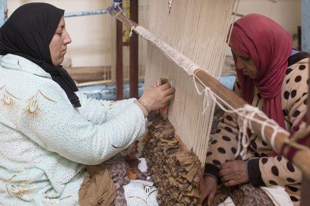 mujeres trabajando en una alfombra american vintage