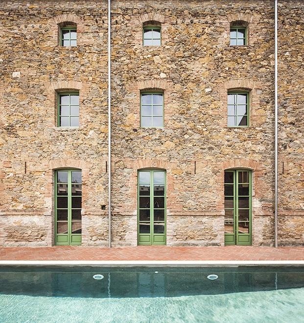 Fachada trasera con muros de piedra de la vieja fábrica de chocolate ahora abierta a un patio con piscina