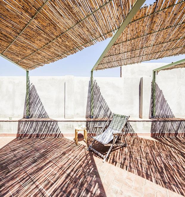 Las nuevas vigas metálicas y el techo de cañizo producen en la terraza un estético juego de luces y sombras
