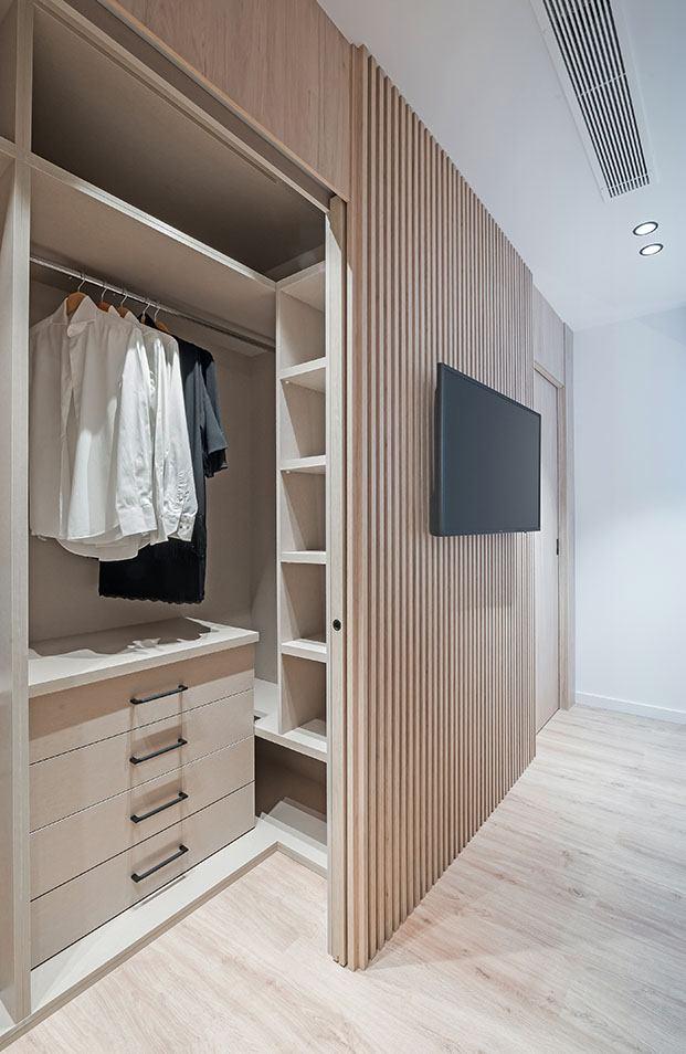 La madera reviste por dentro y por fuera el práctico vestidor del dormitorio principal del apartamento