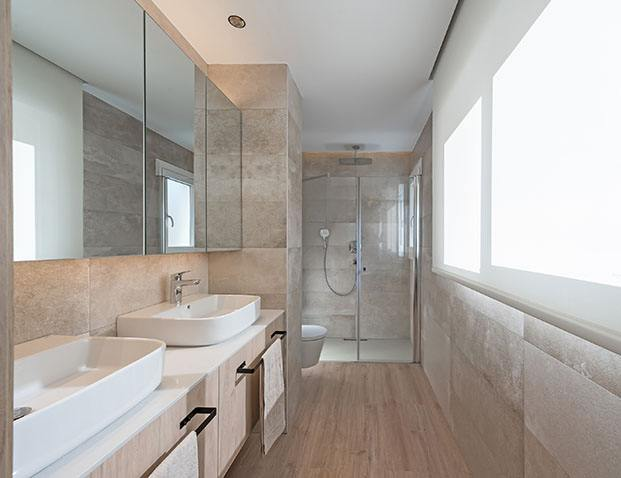 El baño principal del apartameto stá realizado con Silestone un porcelánico en tono piedra para el suelo y muebles hecho a medida