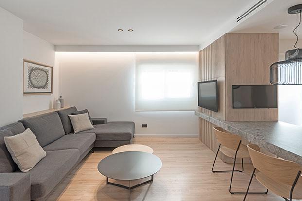 Un amplio espacio acoge a la zona del estar del salón, el comedor y la cocina del apartamento