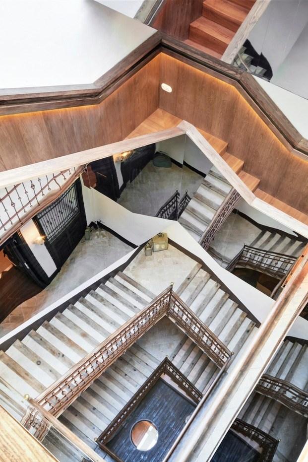 Vista de la escalera interior con espejo por fuera y madera de nogal en su interior