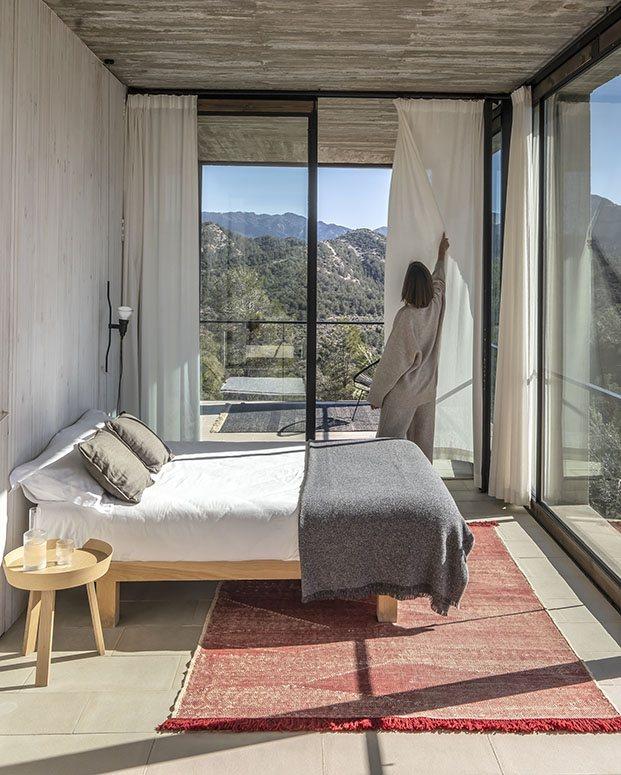 alfombra tonos rojos en habitación con vistas a la montaña. nanimarquina 2020