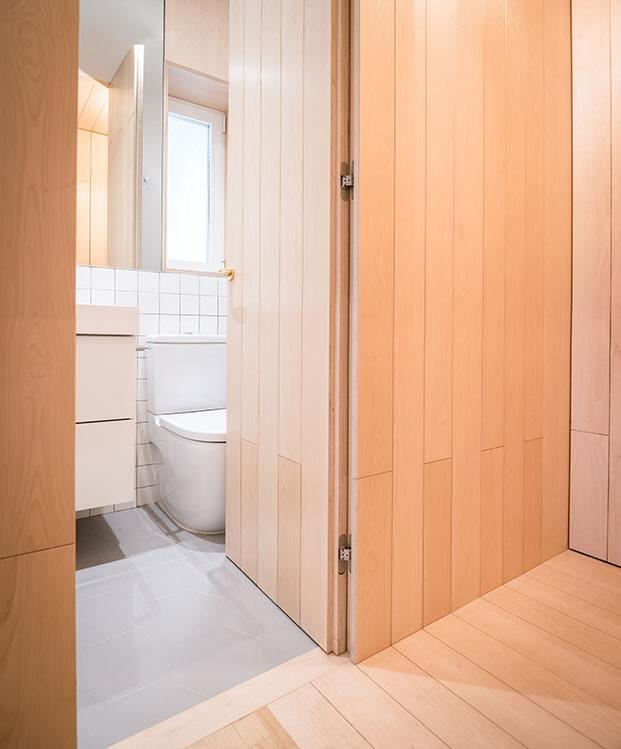 La puerta de entrada al baño queda camuflado con los tablones de  madera