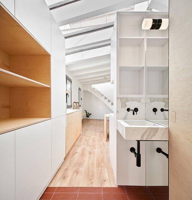 La vista desde el otro lado, el lavabo, que está fuera del dormitorio, la cocina y el salón comedor y al fondo la escalera