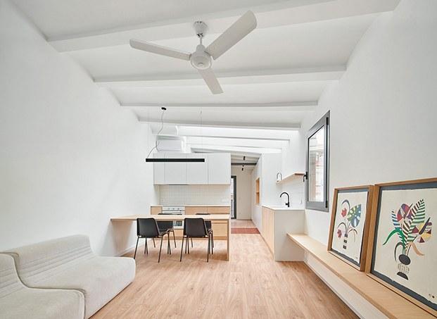 Desde el salón, ambiente abierto que acoge el comedor y la cocina. Al fondo queda el dormitorio