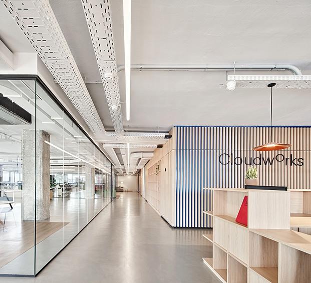 Vista del pasillo central que organiza los espacio de trabajo transparentes de los espacios de trabajo opácos dentro de un núcleo revestido por listones de madera. Suelo continuo de microcemento, pilares de hormigón limpio e instalaciones colgadas en el techo vistas.