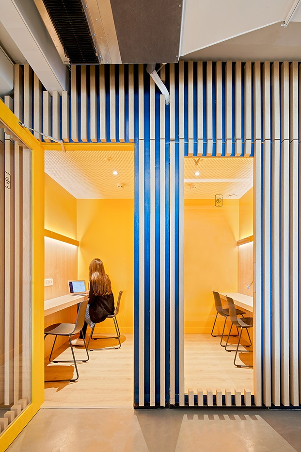 Vista desde el exterior de una sala aislada de trabajo pintada de color mostaza. Puerta abierta y ventana vertical transparente con el resto del paramento de forrado de listones de madera.