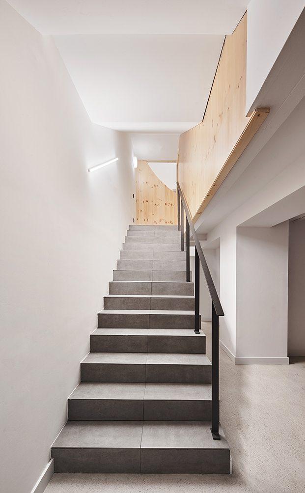 Unas discretas escaleras llevan a la planta sótano de la clínica dental Impress dedicada a servicios