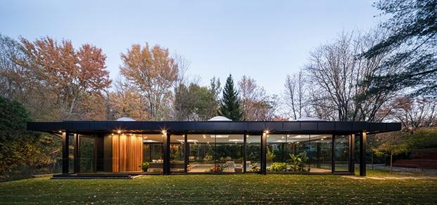 Vista del alzado más largo del pabellón con un entorno de bosque y árboles de gran porte. Prisma con estructura metálica negra y perímetro de vidrio.