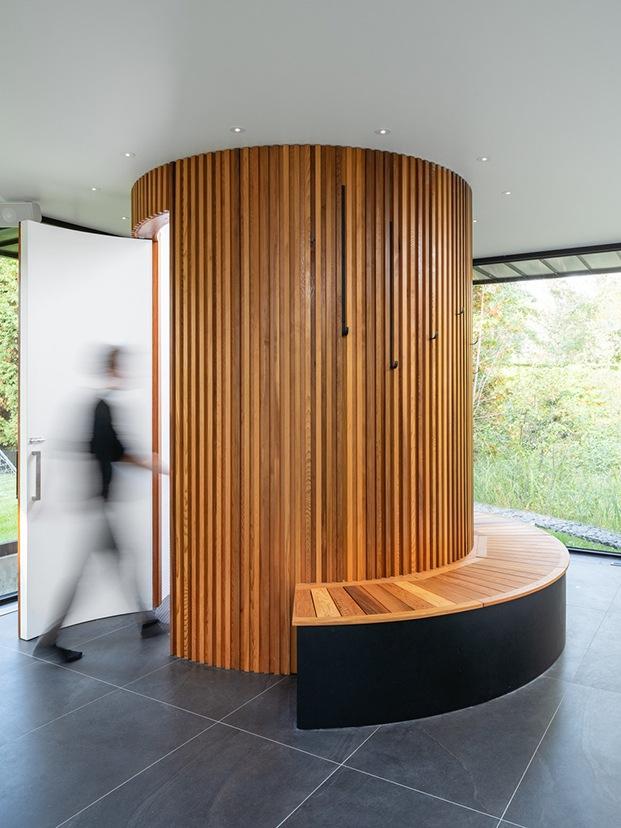 Vista del cilindro forrado con listones de madera de cedro con puerta abierta y persona difuminada en posición de entrar al baño.
