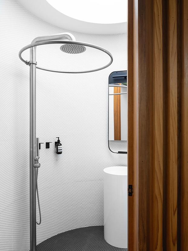 Vista a través de la puerta del interior del baño. Vista parcial del lavabo en columna cilíndrico, espejo rectangular con esquinas redondeadas y ducha en columna exenta de acero inoxidable pulido.