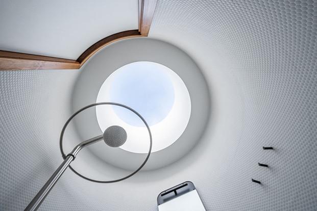Vista hacia el techo con detalle de claraboya y entrada de luz cenital. Espacio en blanco y  revestimiento cerámico tipo gresite circular.