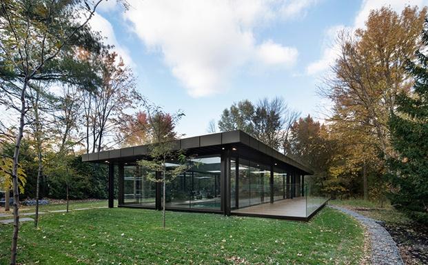 Vista del pabellón desde la esquina con un entorno de bosque y árboles de gran porte. Prisma con estructura metálica negra y perímetro de vidrio.