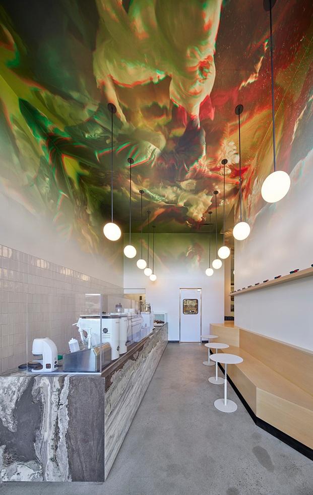 Imagen del interior del local con la barra de mármol al lado izquierdo y banco de madera con mesas redondas blancas al lado derecho de la imagen.