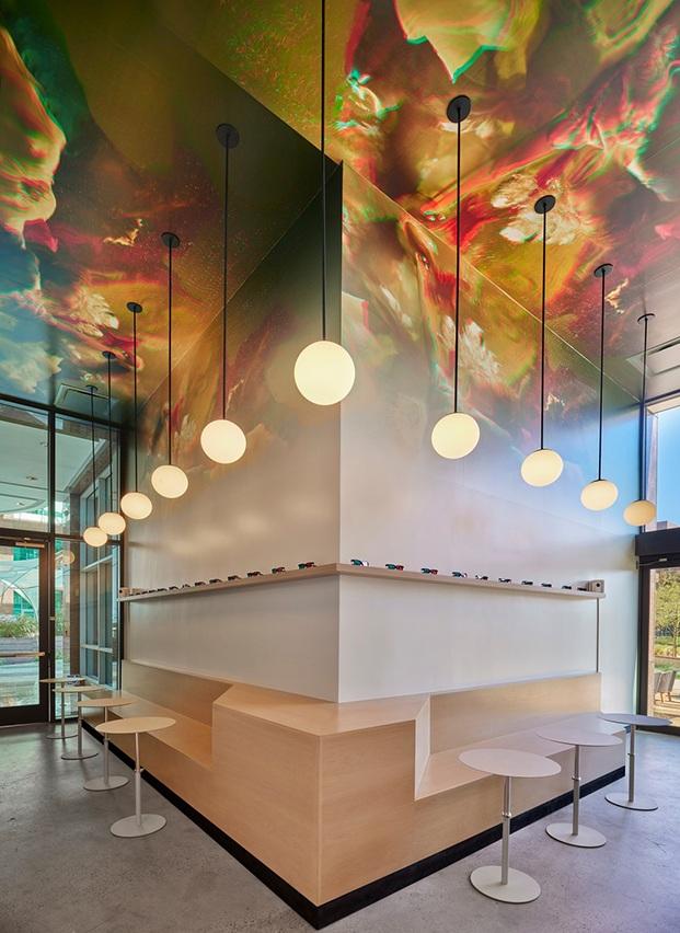 Geometría en L del local con banco perimetral en madera natural y estante corrido con gafas visión 3d. Intervención techo con imagen 3d impresa en vinilos. Iluminación bolas blancas pendientes del techo.