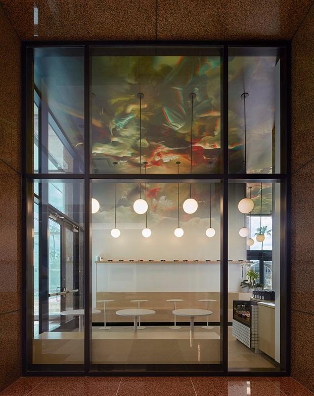 Carpintería de fachada y acceso al local con vistas de la bancada de madera y la intervención en techo con imagen en 3d